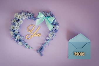 Heart made from hyacinth flowers with mint bow and wooden letters on purple background