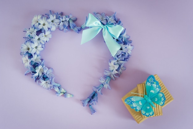 Heart made from hyacinth flowers with mint bow and gift boxes with butterfly on purple background