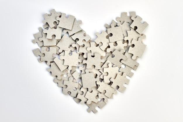 직소 퍼즐로 만든 심장. 흰색 배경 위에 퍼즐 조각에서 만든 심장의 모양.
