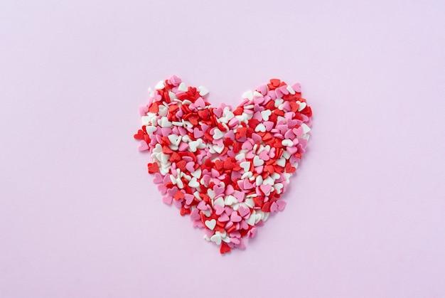 작은 빨간색, 흰색 및 분홍색 설탕 하트로 만든 하트