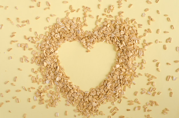 Heart made from oat groats on pastel yellow background