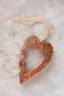 Heart made from tree bark on wooden background