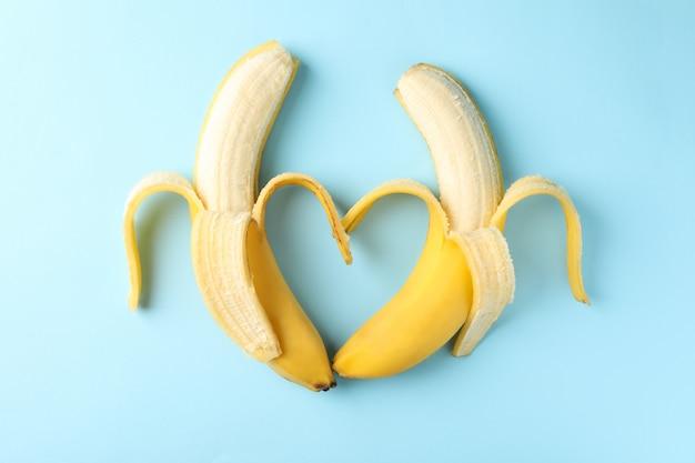 Сердце из бананов на синем фоне. свежие фрукты