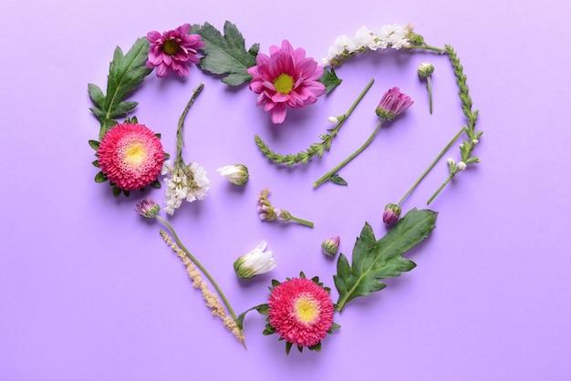 紫色の背景に美しい花と葉で作られたハート