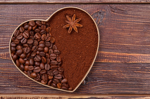 Сердце из кофейных зерен и растворимого кофе. анис на коричневом растворимом кофе. коричневая деревянная поверхность.
