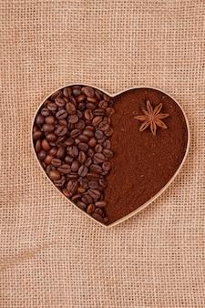 Сердце из кофейных зерен и растворимого порошка с анисом. текстильная ткань бежевого цвета на поверхности.