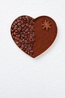 Сердце из кофейных зерен и порошка, изолированные на белом. анис на коричневом порошке растворимого кофе.