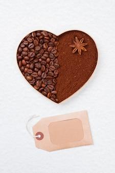 Сердце из кофейных зерен, посыпанное анисом. пустой тег для вашего текста. изолированные на белой поверхности