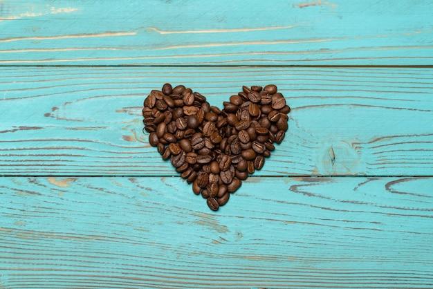 Сердце из кофейных зерен на деревянном столе