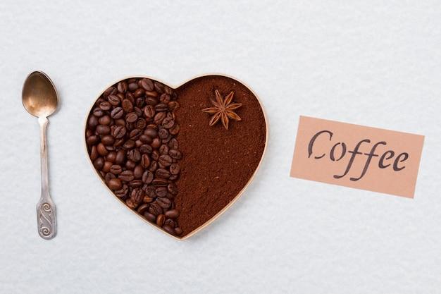 Сердце из кофейных зерен с растворимым кофе и чайной ложкой. изолированные на белой поверхности