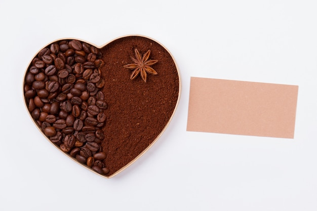 Сердце из кофейных зерен и порошка растворимого кофе. чистый лист бумаги для копирования пространства. белая изолированная поверхность.