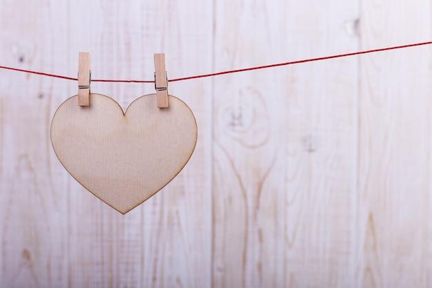 ピンでロープにぶら下がっている手作りのフェルトで作られた心
