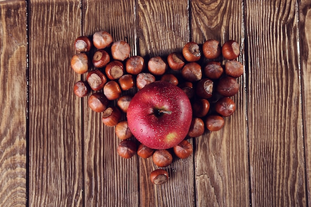 木製のテーブルの上のナッツとリンゴで作られた心、中心部のリンゴに焦点を当てる