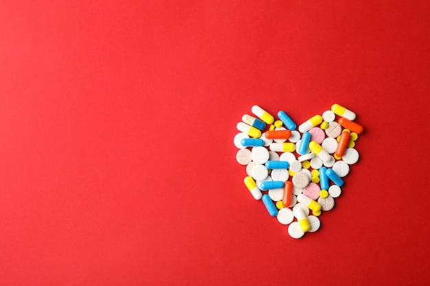 赤い背景、テキスト用のスペースに薬から作られた心。上面図
