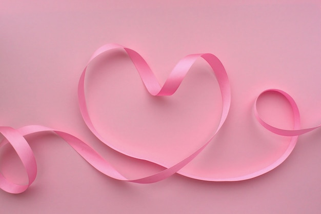 Сердце из розовой ленты на розовом фоне
