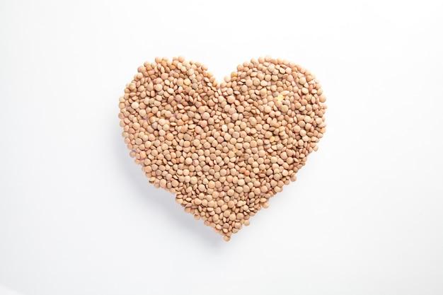 白い壁に生レンズ豆で作られた心臓、健康的な生活と栄養の概念