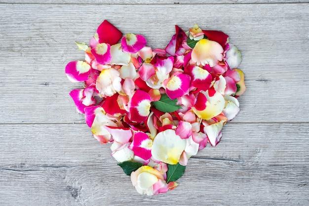 バレンタインデーのための木製の背景にバラの花で作られた心。