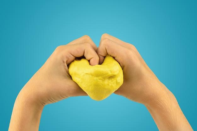어린이의 손에 의해 점액으로 만든 심장. 장난감 스트레스 해소. 손 운동 능력 개발을위한 장난감.