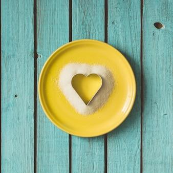 夏の壁にクッキーカッターで砂糖で作られたハート。フラットレイ。