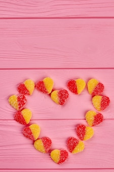 설탕 사탕, 상위 뷰로 만든 심장. 핑크 나무 배경, 복사 공간에 심장 모양을 형성하는 다채로운 사탕. 발렌타인 데이 휴가 개념.