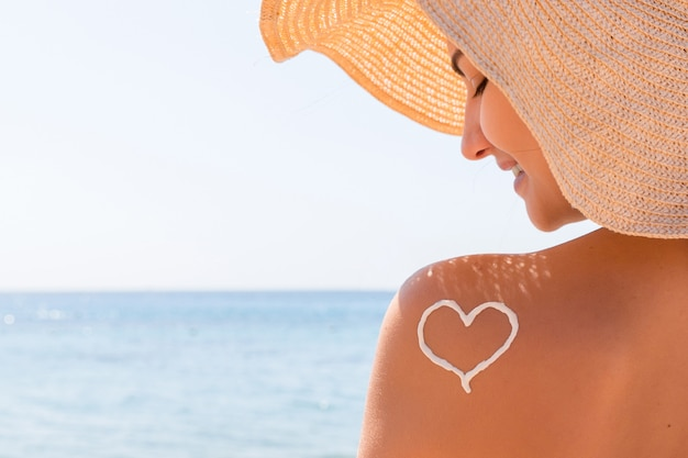 여자의 어깨에 자외선 차단제로 만든 심장