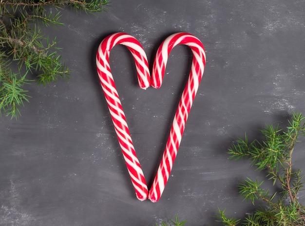 モミの枝とチョークの背景に赤と白のスタッフのお菓子で作られたハート