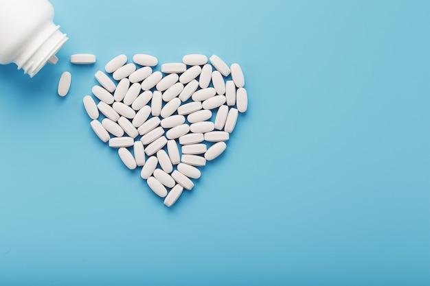 青い背景のボトルから白い丸薬で作られたハート。健康のためのビタミン。テキストの場所