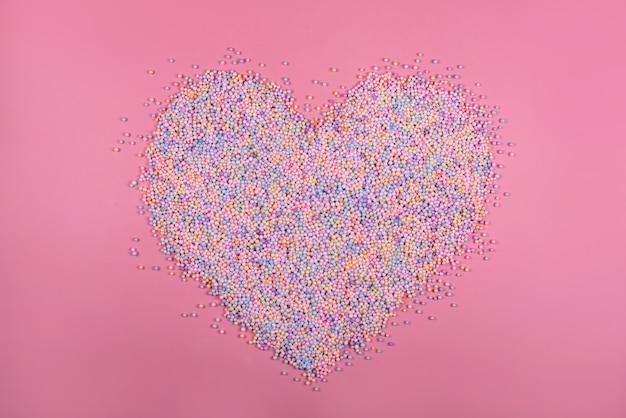 Heart made of pastel color balls on pink styrofoam or polystyrene foam
