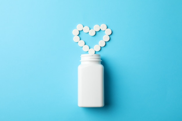 Heart made of pills and blank bottle on blue table