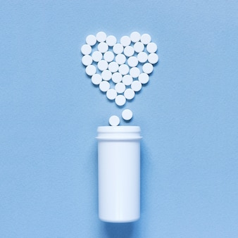 Heart made of pills on the blue textured background