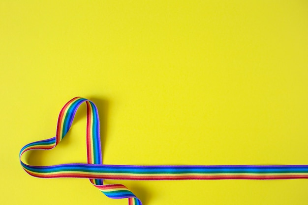 Heart made of rainbow ribbon on a yellow background. lgbt concept