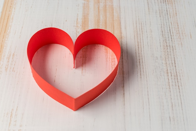 Heart made of ribbon on wooden background.