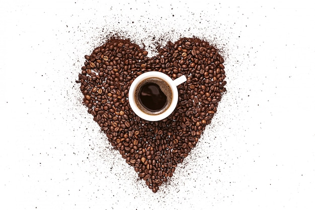 Heart made of roasted coffee beans and ground coffee on a white plate and a cup of freshly brewed coffee