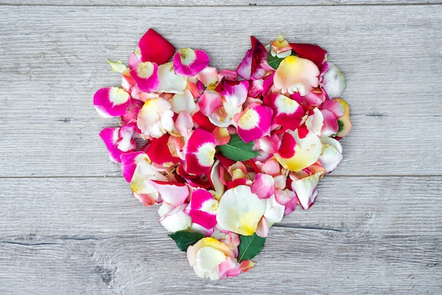Heart made of rose flowers on wooden background for valentines day.