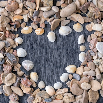 Heart made of sea shells and gravel over wood