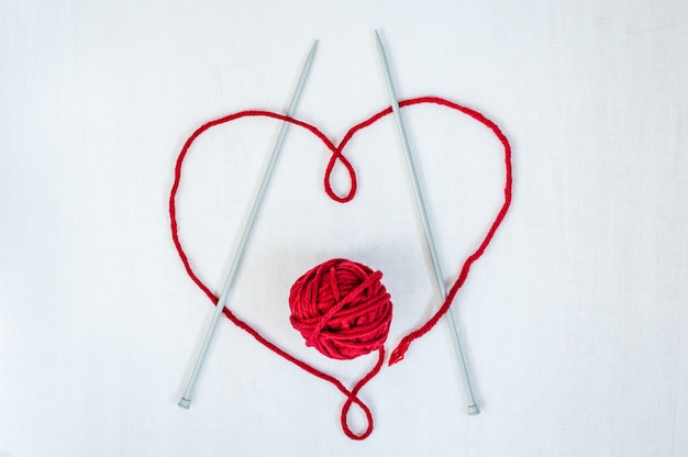 Heart made of thread with woolen yarn and knitting needles on white wooden background.