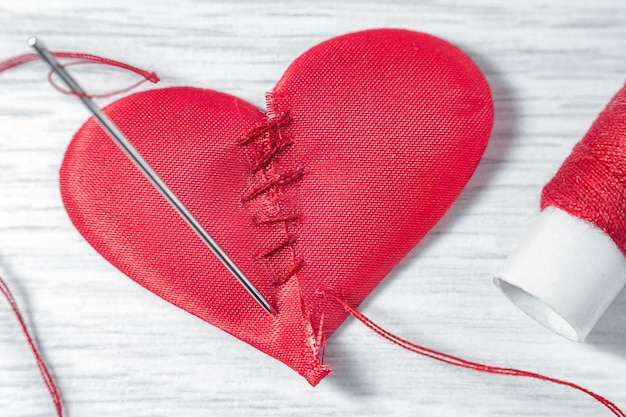 Heart made of two halves on a white wooden table. next to it is a needle with a threaded thread and a spool with red threads.