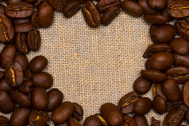 Heart made with coffee beans stacked against burlap canvas Premium Photo