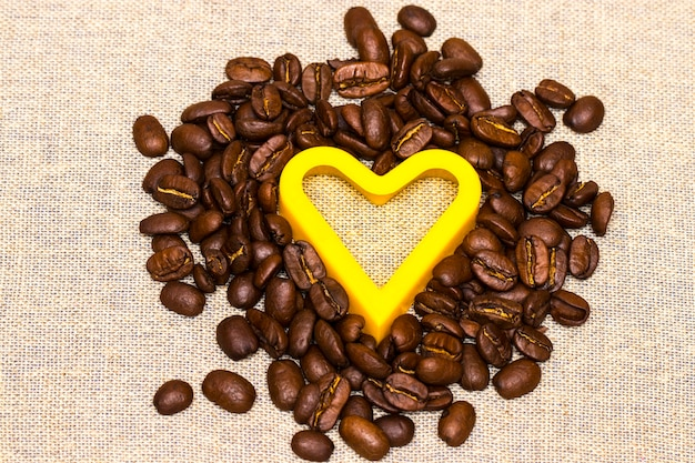 Heart made with coffee beans stacked against burlap canvas.