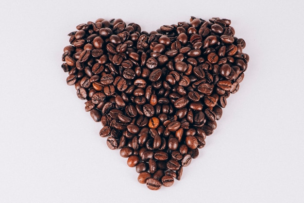 Heart made with coffee beans on white background. conceptual.