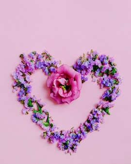 Heart made with lavender and pink flower on pink background