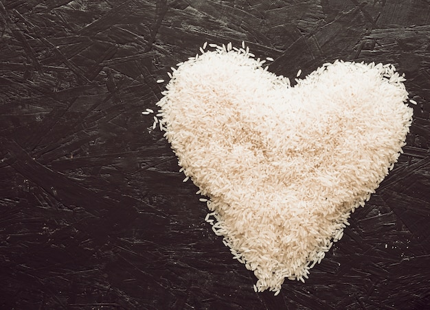 Heart made with rice grains on textured background