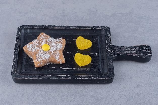 Marmellate di cuore e biscotto stella su un vassoio sulla superficie di marmo