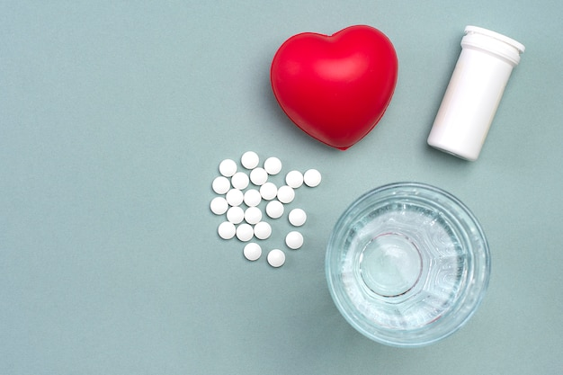Heart, medical pills, cardiogram, glass of water, capsules on gray background. concept of healthy heart flat lay top view