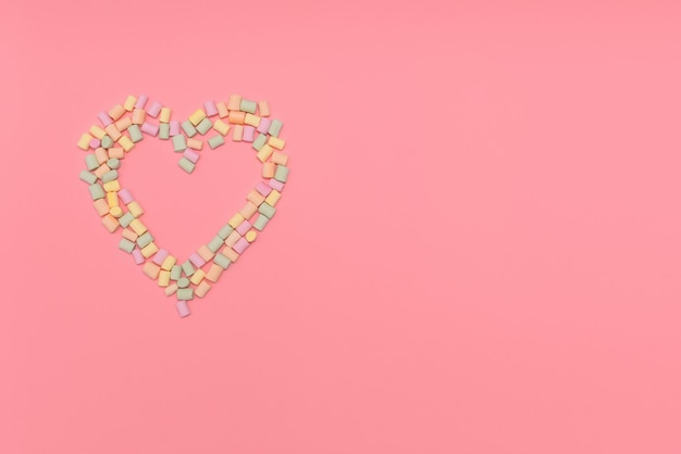 Heart of multi colored marshmallows isolated on pink background. love, congratulation concept.