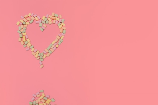Heart of multicolored marshmallows isolated on pink background