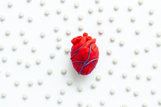 Heart near pills on white background top view