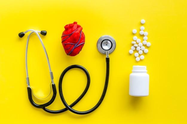 Heart near pills on yellow top view