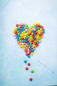 Сердце из шоколадных круглых конфет в сахарной глазури на голубом бетонном столе. день святого валентина. выборочный фокус. вид сверху. место для текста.