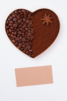 Сердце кофейных зерен и чистый лист бумаги для космоса экземпляра. белая изолированная поверхность.